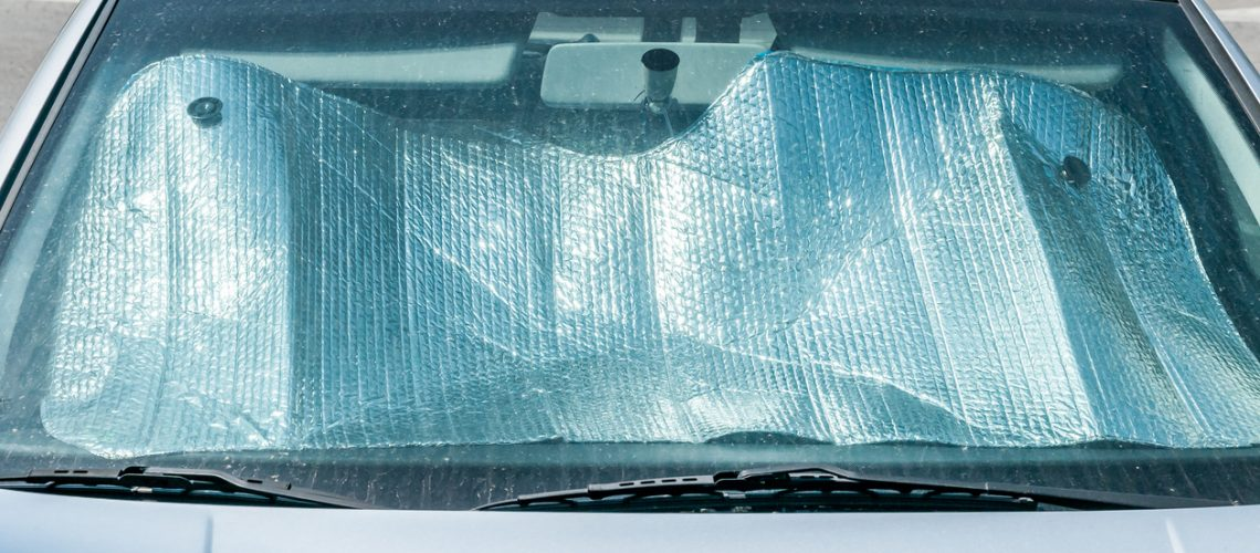 Sun reflector on the windscreen or windshield as protection of the car plastic indoor panel from direct sunlight and heat